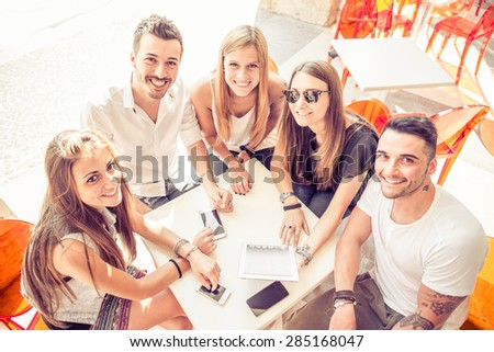 Group of happy and smiling friends sitting in a bar and looking at the camera, many digital devices on the table - Group of students meet in a cafe outdoors - stock photo
