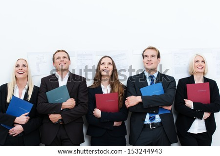 Group of happy applicants for a job sitting in a long row with smiles on their faces clutching their curriculum vitae - stock photo