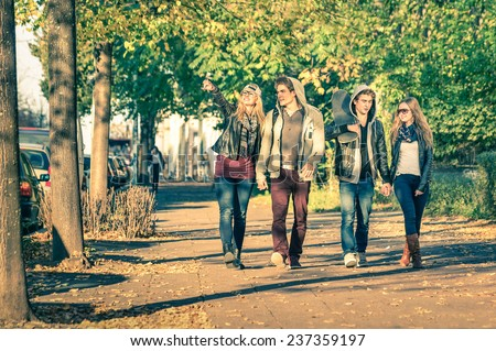 Group of happy best friends with alternative fashion look walking at the park - Hipster tourists having fun outdoors in sunny winter day - University students during a break hanging out together - stock photo