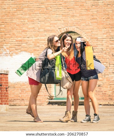 Group of happy best friends with shopping bags taking a selfie in the city  - Girlfriends walking and having fun in the summer around the old town - University students during a break in a sunny day - stock photo