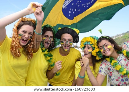 Group of happy Brazilian soccer fans commemorating victory, with the flag of Brazil swinging in the air. - stock photo
