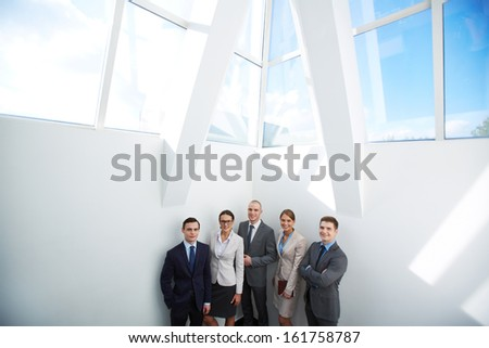 Group of happy business partners looking at camera in office - stock photo