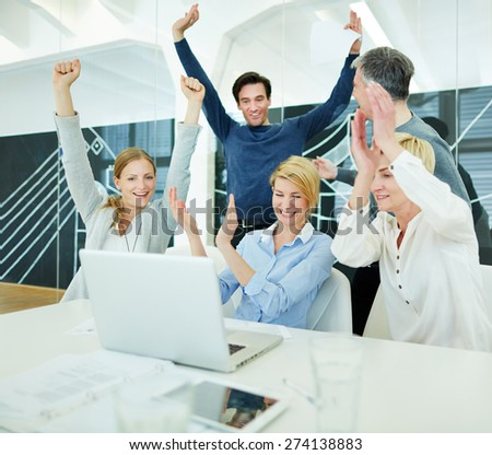 Group of happy business people cheering in office in front of computer - stock photo