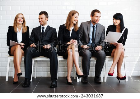 Group of happy business people sitting in waiting room - stock photo