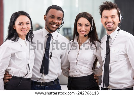 Group of happy, cheerful call center workers are smiling and looking at the camera. - stock photo