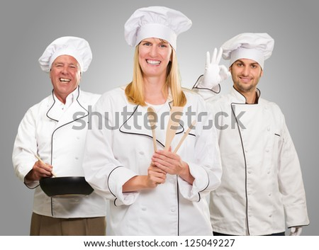 Group Of Happy Chef's At Work On Grey Background - stock photo