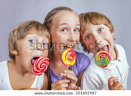 Group of happy children eating candy - stock photo