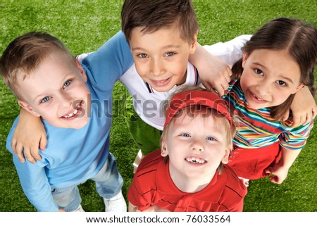 Group of happy children on green grass looking at camera - stock photo