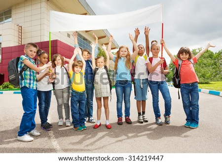Group of happy children with arms up hold placard - stock photo