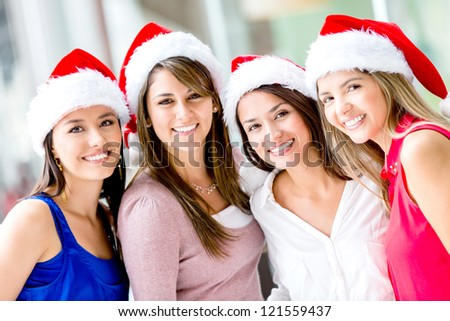 Group of happy Christmas women wearing Santas hat - stock photo