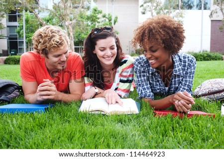 group of happy college students lying in the grass with notebooks - stock photo