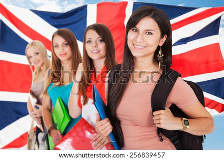 Group Of Happy College Students Standing In Front Of British Flag - stock photo