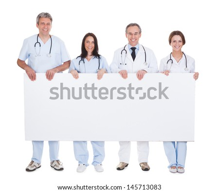Group Of Happy Doctor Standing In A Row Holding Placard - stock photo