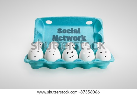 Group of happy eggs with smiling faces representing a social network. Ten white eggs in a carton box. On a gray background - stock photo