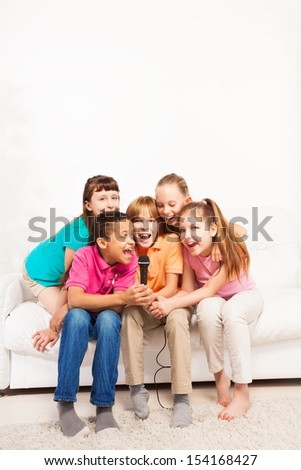 Group of happy exited diversity looking kids, boys and girls, singing together sitting on the coach in living room - stock photo
