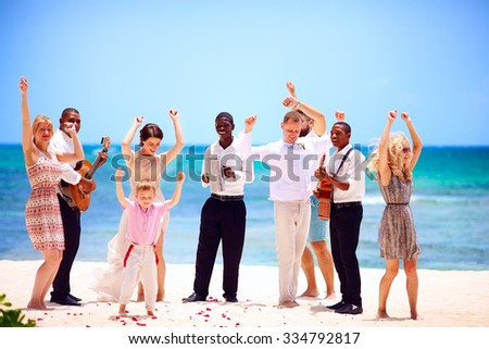 group of happy family on celebration the exotic wedding with musicians, on tropical beach - stock photo