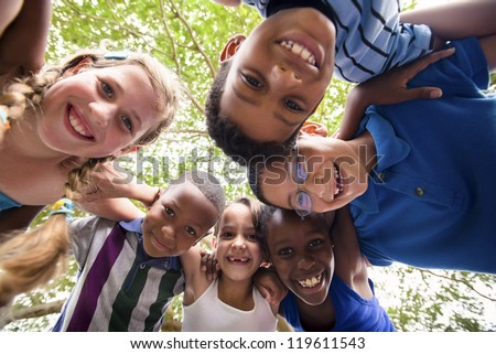 Group of happy female and male kids having fun and hugging around the camera. Low angle view - stock photo