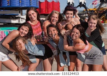 Group of 8 happy female teens together at a carnival - stock photo