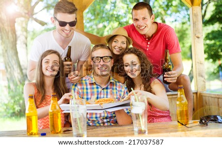 Group of happy friends drinking and eating pizza in pub garden - stock photo
