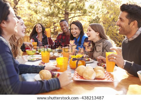 Group of happy friends eat and laugh at a table at a barbecue - stock photo