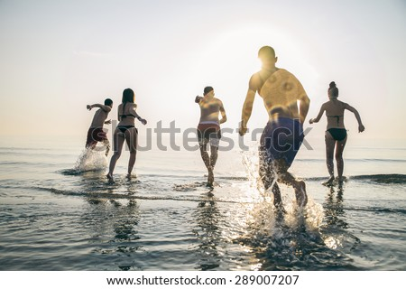 Group of happy friends running in to water at sunset - Silhouettes of active people having fun on the beach on vacation - Tourists going to swim on a tropical island - stock photo
