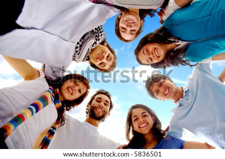 group of happy friends smiling with heads together outdoors with a blue sky in the background - stock photo