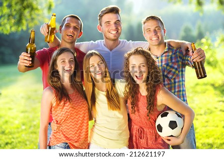 Group of happy friends spending free time together in park and drinking beer - stock photo
