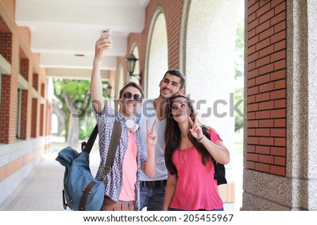 Group of happy friends taking a selfie by smart phone in campus , caucasian - stock photo