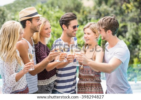 Group of happy friends toasting champagne glasses outdoors - stock photo