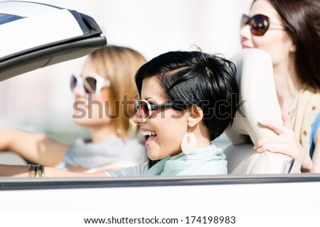 Group of happy girls in the car. Little trip of teenage ladies - stock photo