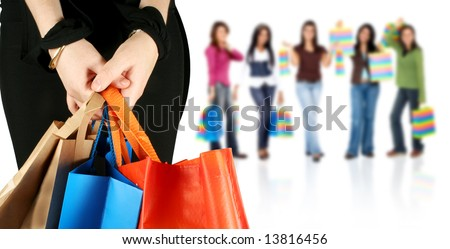 group of happy girls or women smiling and carrying shopping bags isolated over a white background - stock photo