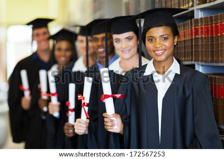 group of happy graduates holding diploma in library - stock photo