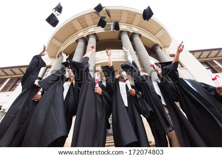 group of happy graduates throwing graduation hats in the air celebrating - stock photo
