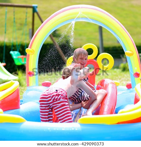 Group of happy healthy kids having fun in inflatable water center. Children enjoying summer holidays playing in the pool at the backyard in the garden. - stock photo