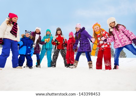Group of happy kids, having fun on snow day, holding hands and walking in circle - stock photo