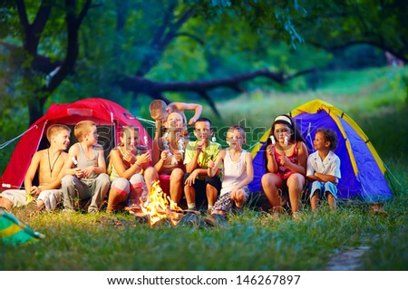 group of happy kids roasting marshmallows on camp fire - stock photo