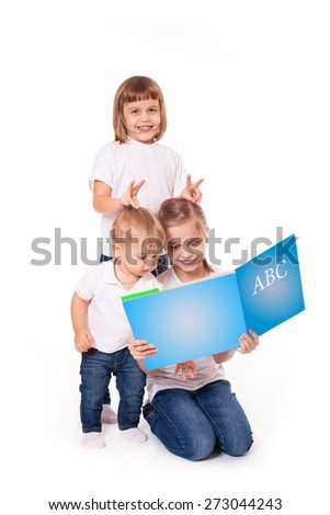 Group of happy kids sisters and brother reading book, isolated on white - stock photo
