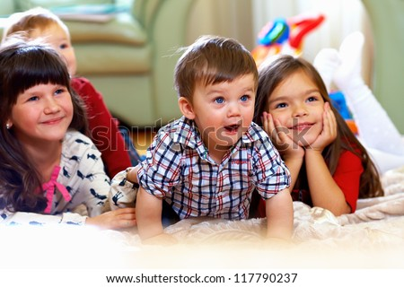 group of happy kids watching tv at home - stock photo