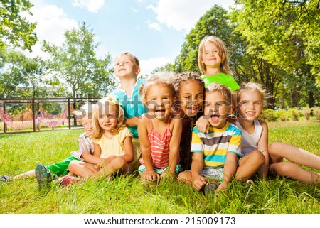Group of happy little kids on the lawn in park - stock photo