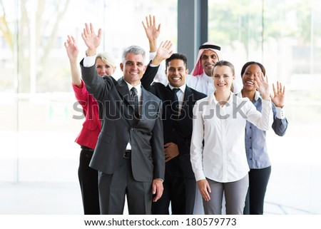 group of happy multicultural businesspeople waving - stock photo