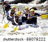 Group of happy people with guide whitewater rafting and rowing on river - stock photo