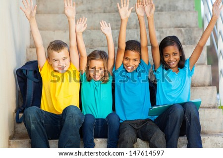 group of happy primary students with hands raised sitting outdoors - stock photo