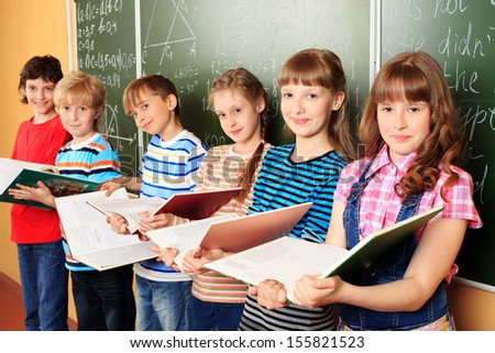 Group of happy schoolchildren standing with books at a classroom. Education. - stock photo