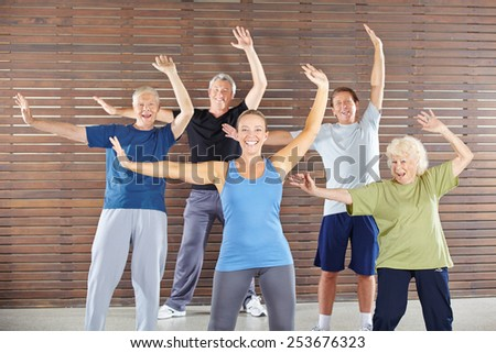 Group of happy seniors dancing and exercising in gym class - stock photo