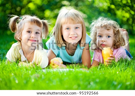 Group of happy smiling children playing outdoors in spring park - stock photo