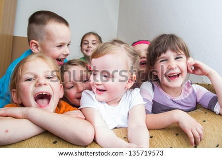 Group of happy smiling kids sitting together - stock photo