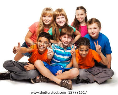 Group of happy smiling kids sitting together and playing - boys and girls black and Caucasian, isolated on white - stock photo