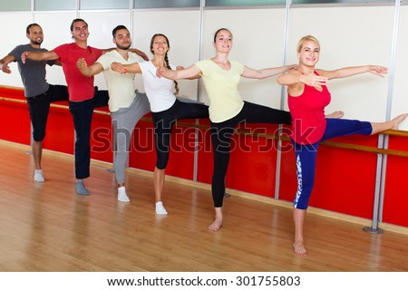 Group of happy spanish men and women practicing at the ballet barre - stock photo