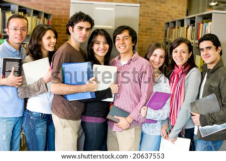 group of happy students in a library smiling - stock photo