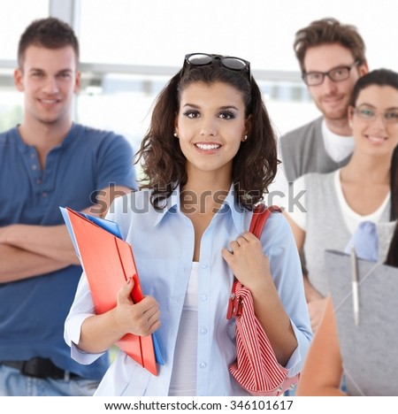 Group of happy students on school corridor looking at camera, smiling. - stock photo